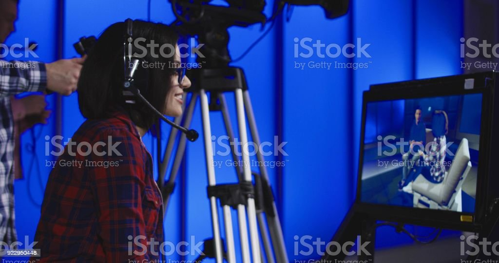Woman giving instructions in a newsroom stock photo