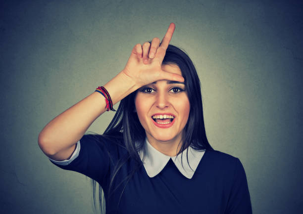 woman giving loser sign looking at you woman giving loser sign looking at you, making fun isolated on gray wall background antagonize stock pictures, royalty-free photos & images