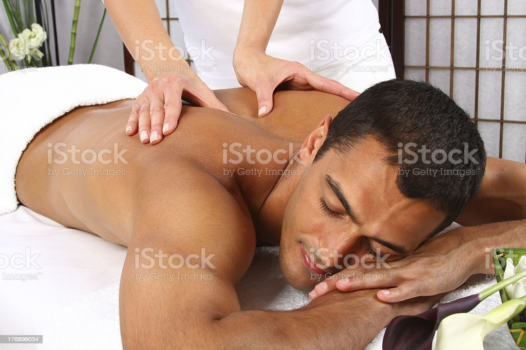Woman giving man a back massage on massage table stock photo
