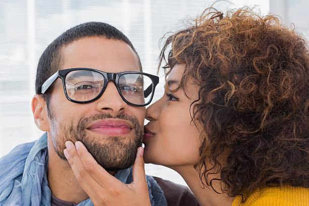 woman giving man kiss on the cheek - brunette woman eyeglasses kiss man foto e immagini stock