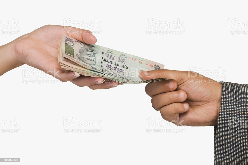 Woman giving money to a man stock photo