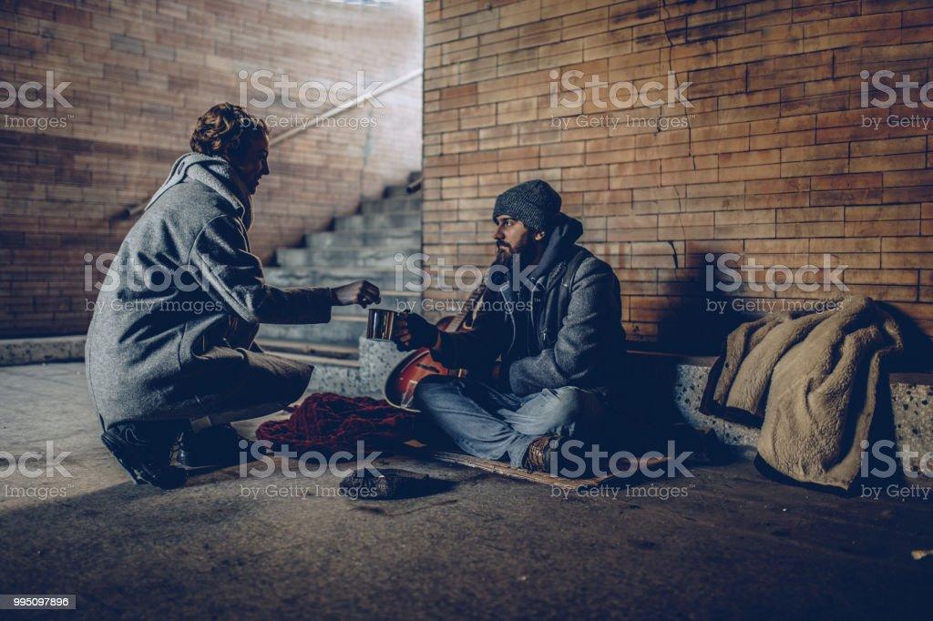 Mulher dando dinheiro ao mendigo homem - foto de acervo