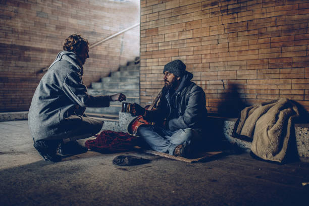 woman giving money to beggar man - homelessness stock photos and pictures