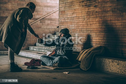 Woman Giving Money To Beggar On Street