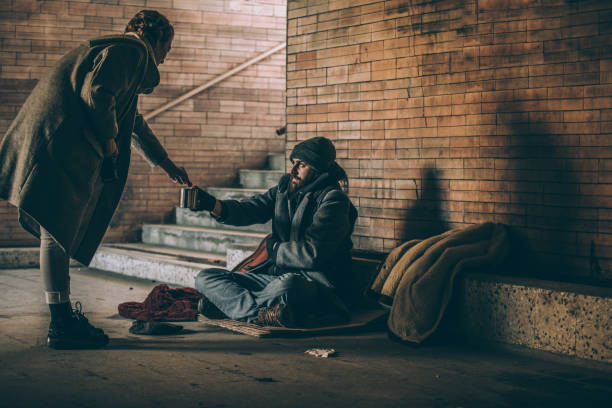 Woman Giving Money To Beggar Woman Giving Money To Beggar On Street homelessness stock pictures, royalty-free photos & images