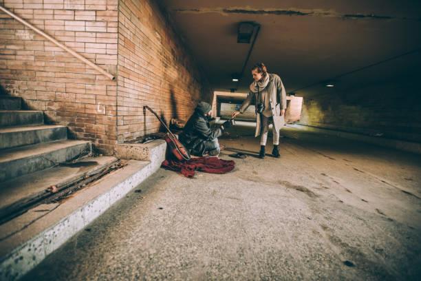 frau geld geben, die obdachlos person - bettler stock-fotos und bilder
