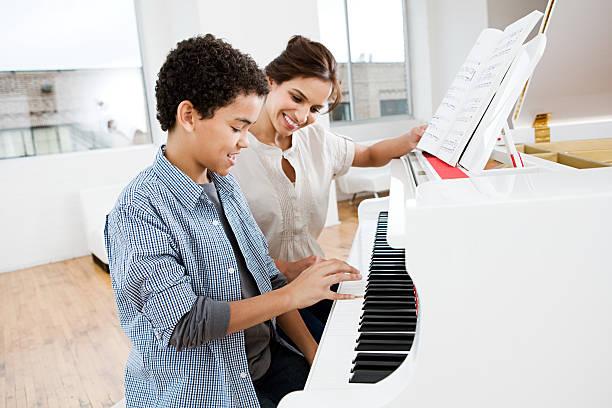 femme donner leçon de piano pour garçon - piano photos et images de collection