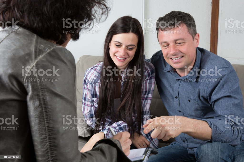 Woman giving plan to couple purchasing new house stock photo