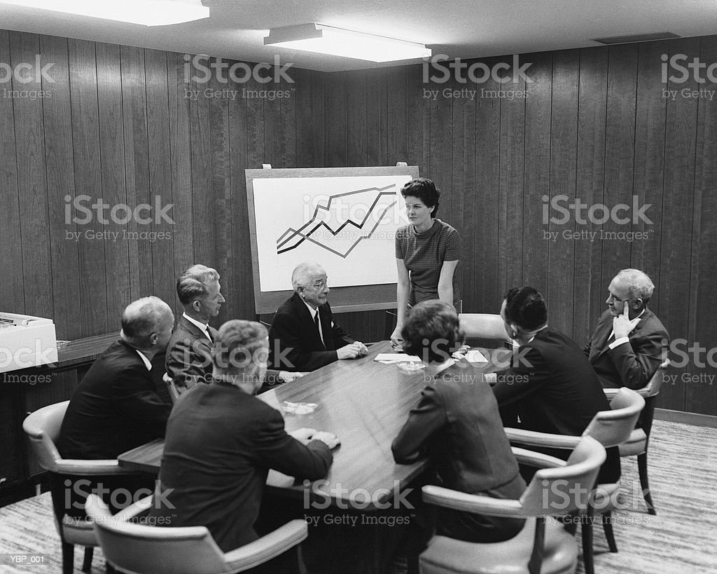 Woman giving presentation to group in meeting royalty-free stock photo