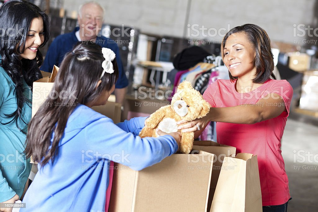Woman giving teddy bear to needy family at donation center stock photo