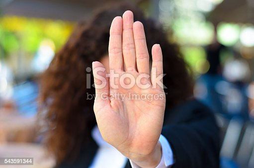 Woman giving the halt or stop sign holding up her palm in an authoritative manner indicating she has had enough, no access or halt immediately