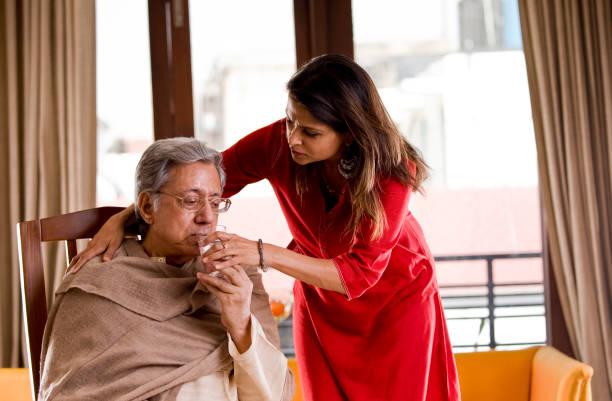 Frau gibt ihrem kranken Vater Wasser – Foto