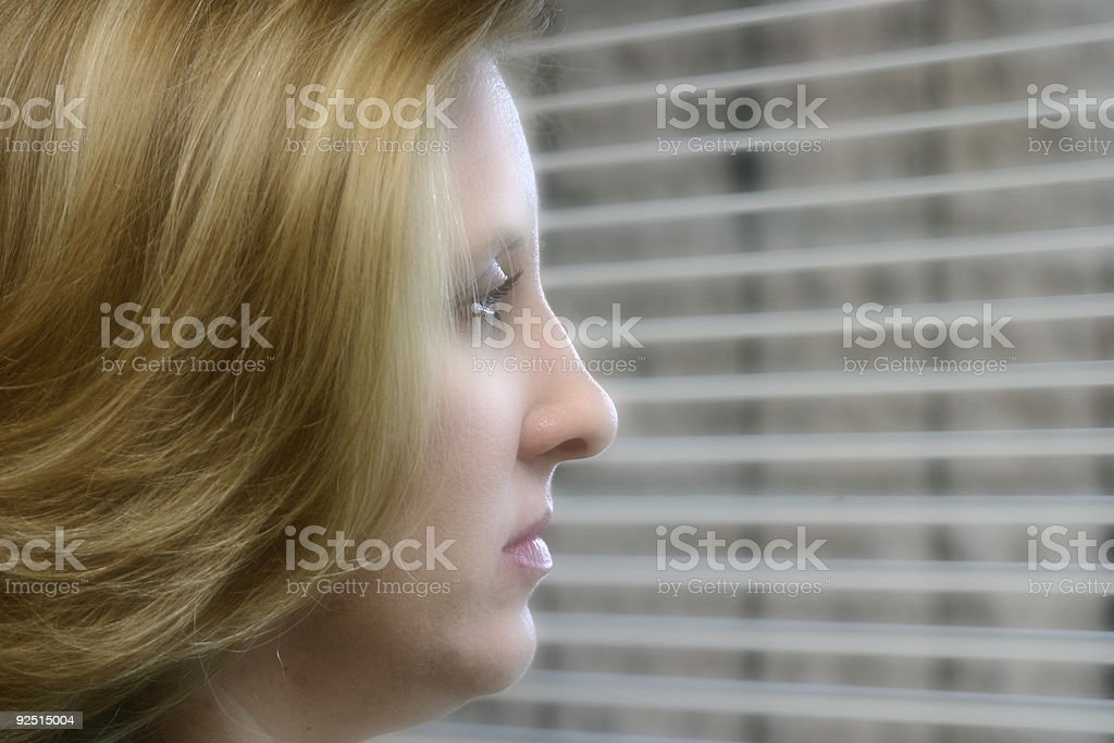 Woman glancing out window royalty-free stock photo