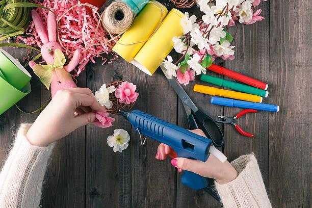 Woman glue handmade flowers with melt gun stock photo