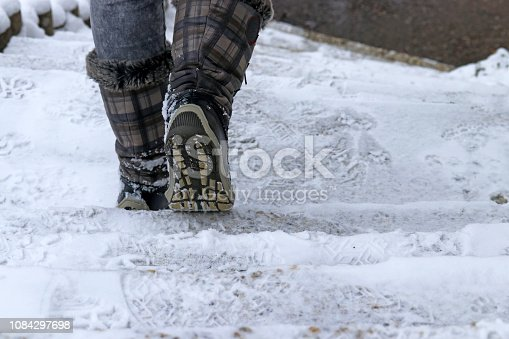 istock A woman goes down a staircase in winter 1084297698