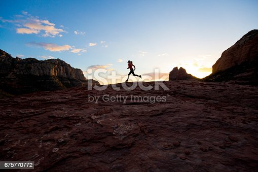 A woman runs a popular trail at the end of the day in Sedona, Arizona, USA.