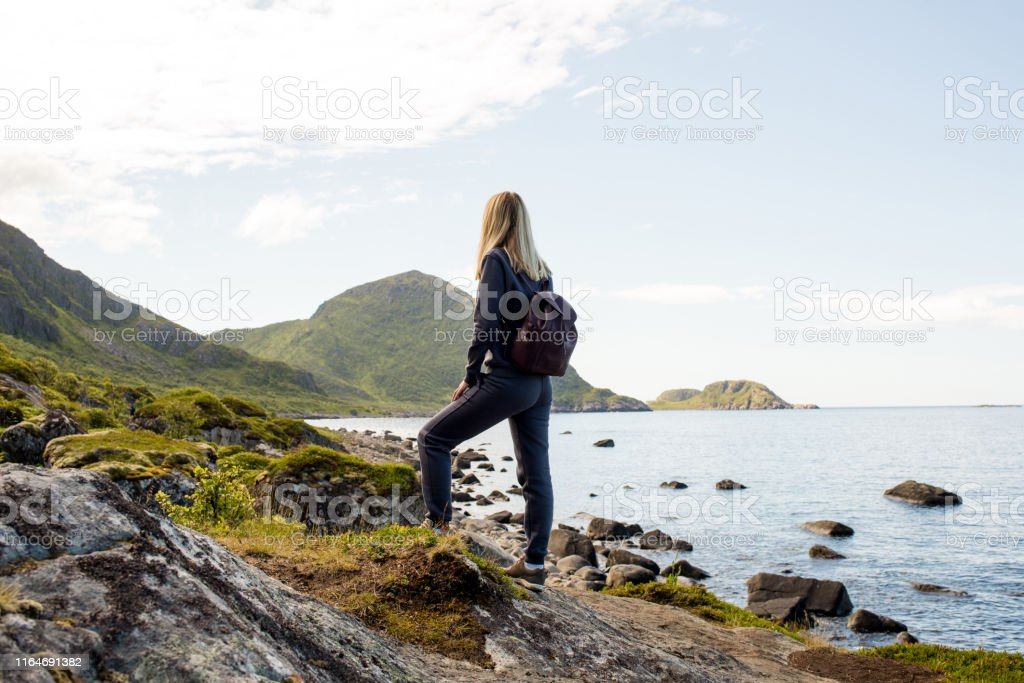 Woman goes on tourist hiking trail along ocean and mountains in...