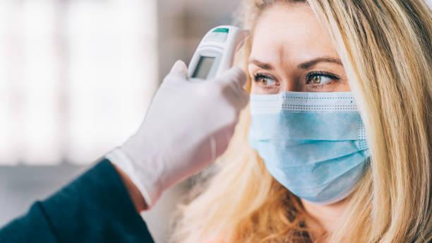 Frau durchläuft eine Temperaturkontrolle, bevor sie ins Büro geht und während COVID-19 eine medizinische Gesichtsmaske trägt – Foto
