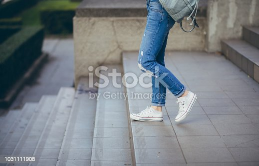 Young woman with backpack going down a staircase
