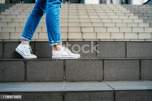 Young woman with backpack going down a staircase.