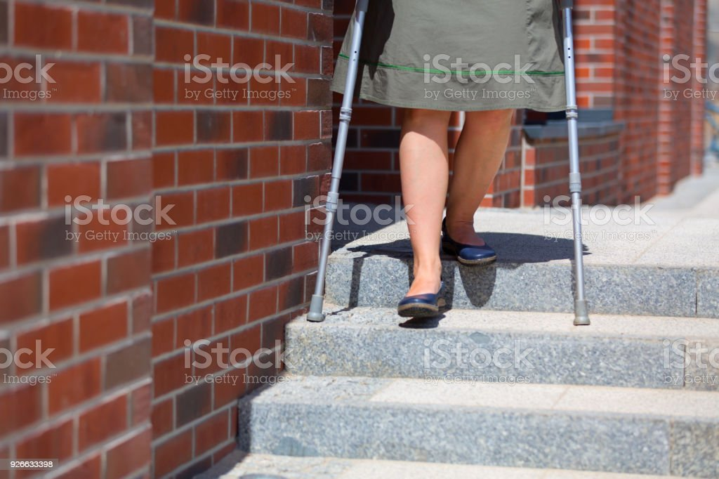 woman going down the stairs using crutches stock photo