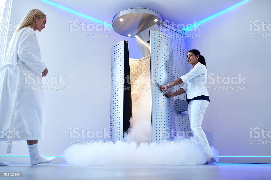 Woman going for whole body cryotherapy Full length portrait of nurse opening the door of cryosauna, with woman in bathrobe at the clinic. Female going for cryotherapy treatment in freezing cabinet. Adult Stock Photo