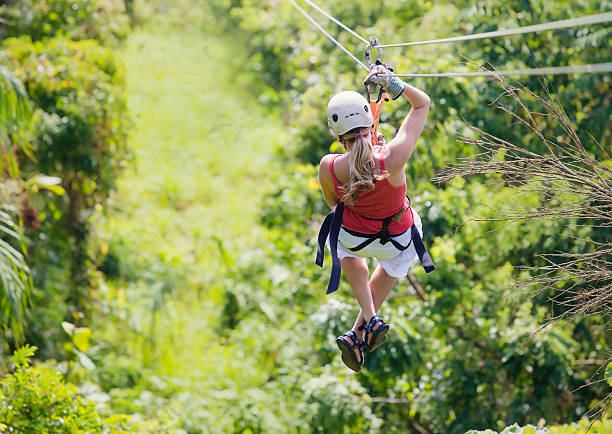 Woman going on a jungle zipline adventure Woman enjoying a fun zip line tour in the jungle while on vacation zip line stock pictures, royalty-free photos & images