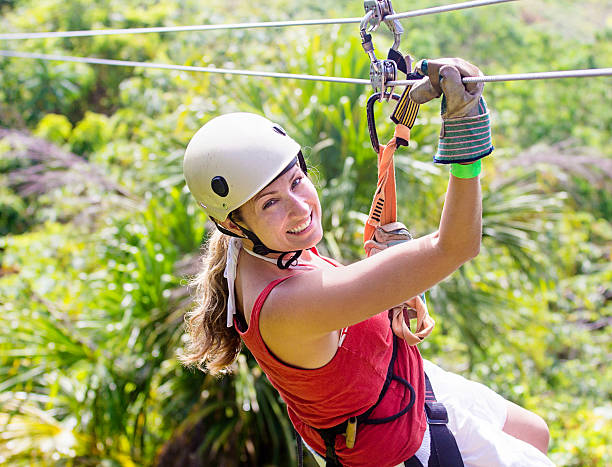 Woman going on a jungle zipline adventure Woman smiles while enjoying a fun zip line tour in the jungle while on vacation zip line stock pictures, royalty-free photos & images