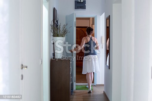 Back view of a woman opens the front door, leaving the apartment.