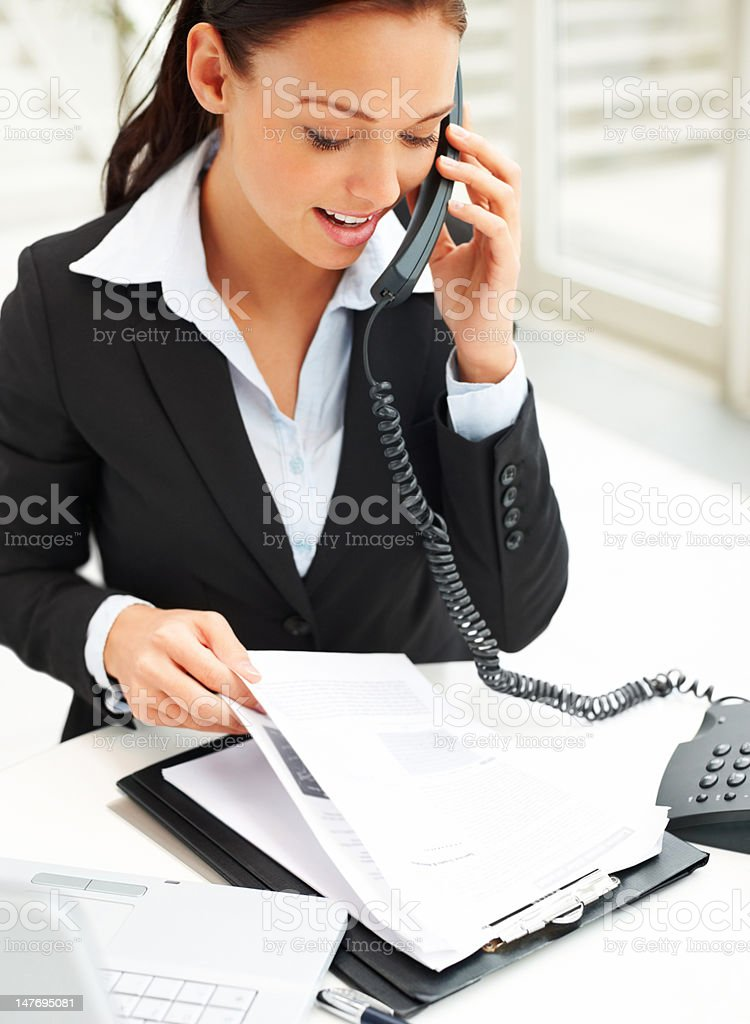 Woman going over documents while on the phone royalty-free stock photo