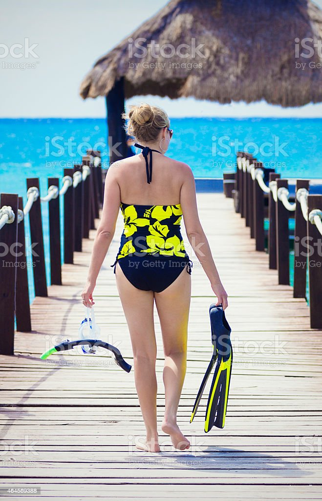 Woman going snorkeling while on a tropical vacation stock photo