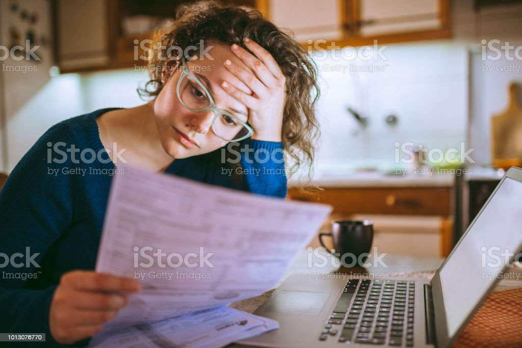 Woman going through bills, looking worried stock photo