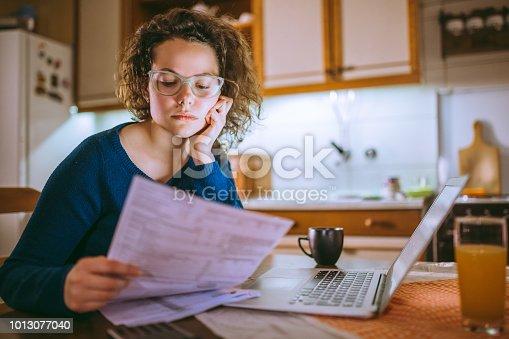 693910734 istock photo Woman going through bills, looking worried 1013077040