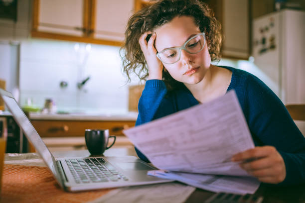 woman going through bills, looking worried - tenant stock photos and pictures