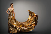 Woman Gold Dress, Fashion Model in Long Waving Fluttering Gown, Young Girl Beauty Studio Portrait over gray background