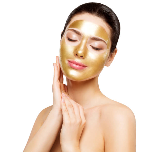 Woman Gold Mask, Beautiful Model with Golden Skin Cosmetic touch Face, Beauty Skincare and Treatment stock photo
