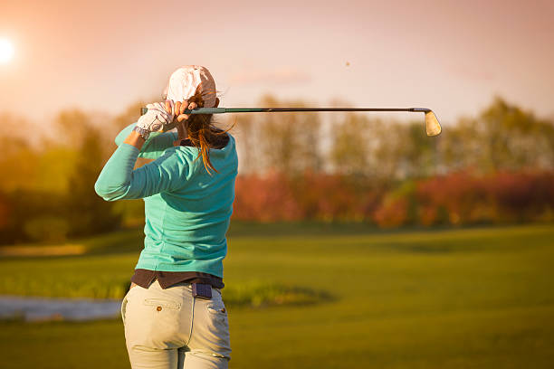 Woman golf player hitting ball. stock photo