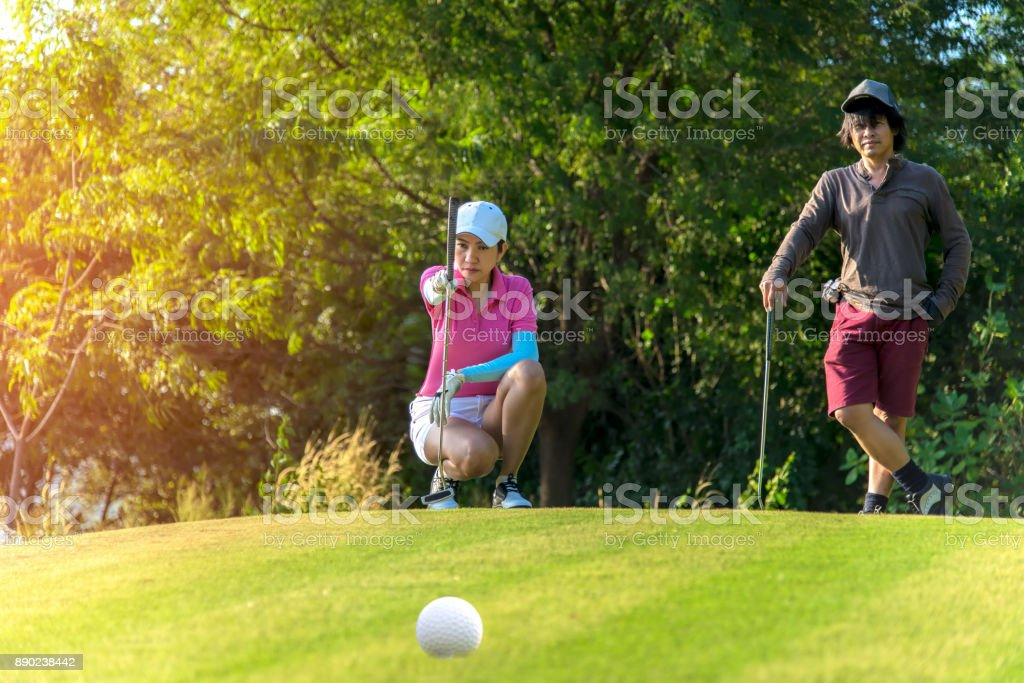 Woman golf player squatting to analyze the green for putting the golf...