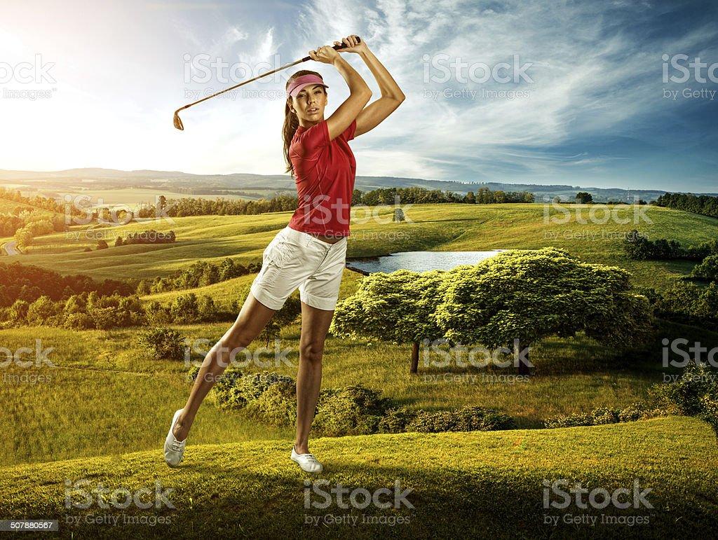 Woman golfer hitting the ball on  background scenery  beautiful stock photo