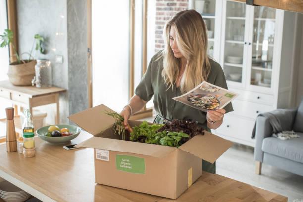 la donna ha ricevuto il pacco dal servizio di consegna dei pasti. - grocery home foto e immagini stock