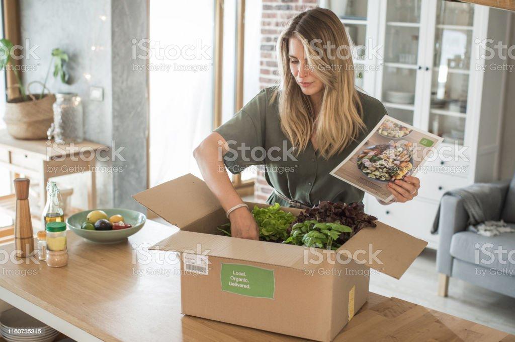 Kobieta dostała paczkę z usługi dostawy posiłków. - Zbiór zdjęć royalty-free (Artykuły spożywcze)