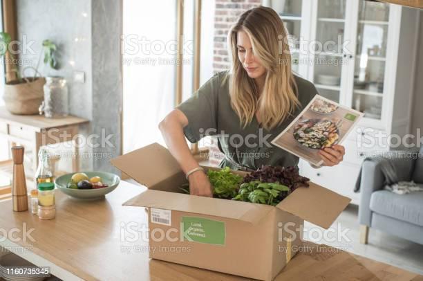 Kobieta Dostała Paczkę Z Usługi Dostawy Posiłków - zdjęcia stockowe i więcej obrazów Artykuły spożywcze