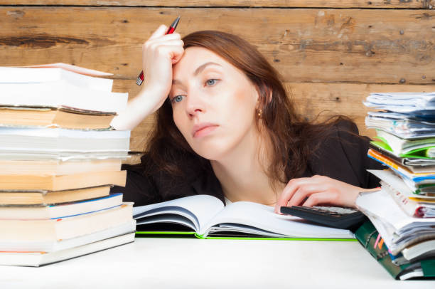 Woman got tired of working and studying next to the stack of papers and books. Work and study concept stock photo