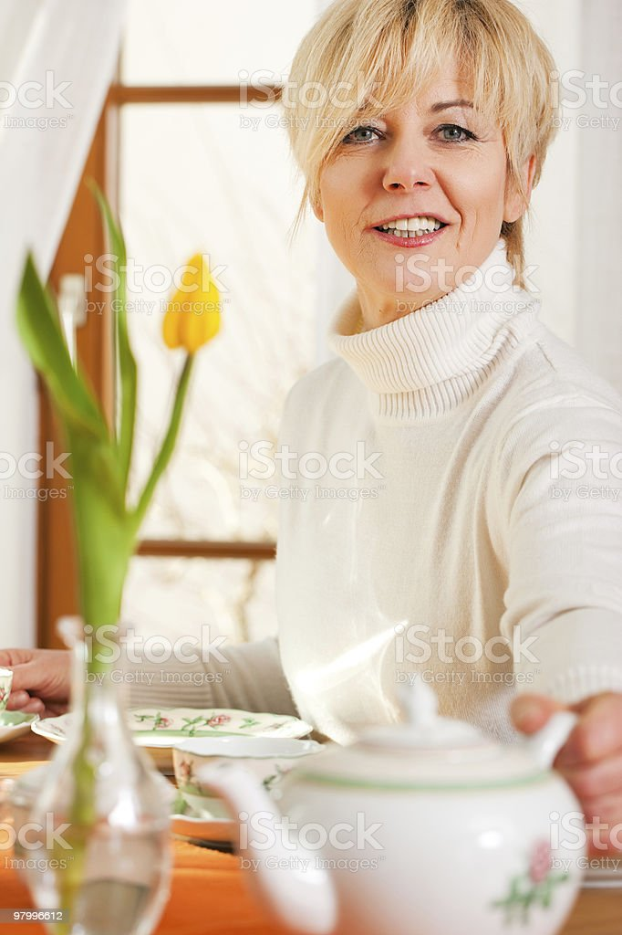 Woman grabbing coffee or tea pot royalty-free stock photo