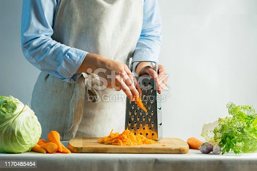 istock Woman grates fresh carrots for cooking salad or for salting cabbage natural background. Vegetarian food concept. 1170485454