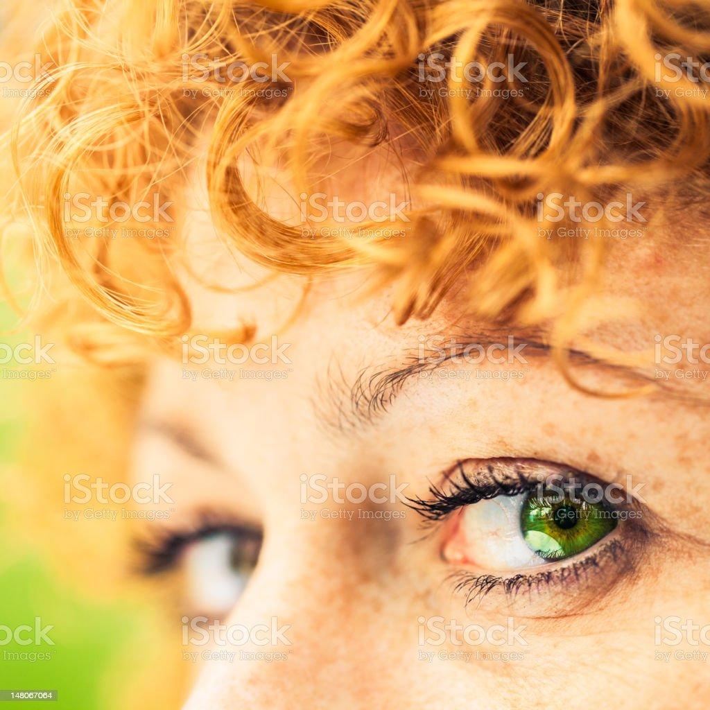 Woman green eye and curly red hair stock photo