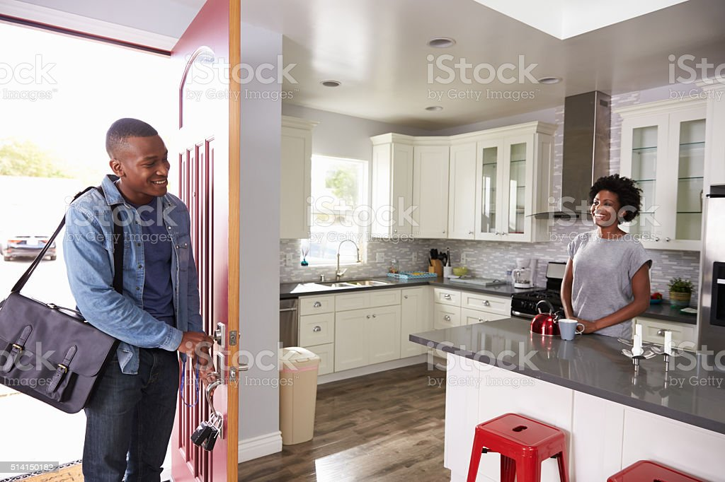 Woman Greeting Man Returning Home From Work stock photo