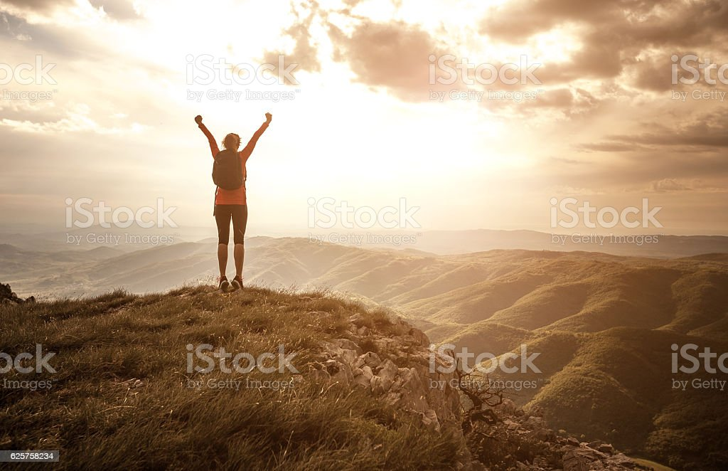 Woman Greeting the Sun on the Top of the Hill stock photo