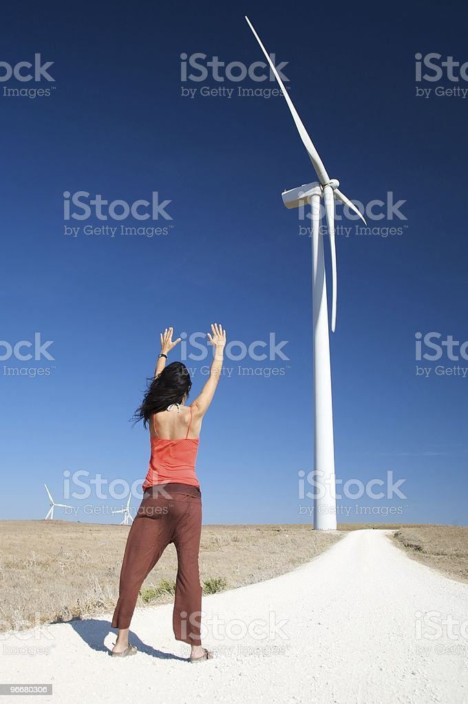 woman greeting wind energy mill royalty-free stock photo