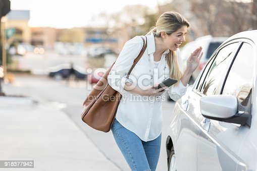 918377954 istock photo Woman greets ride share driver 918377942